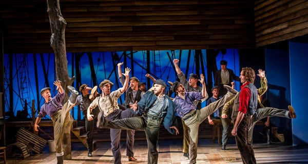 Opera North's Carousel. Michael Rouse as Jigger (centre) and Michael Todd Simpson as Billy Bigelow (right) with the Chorus of Opera North and dancers. Photo Robert Workman